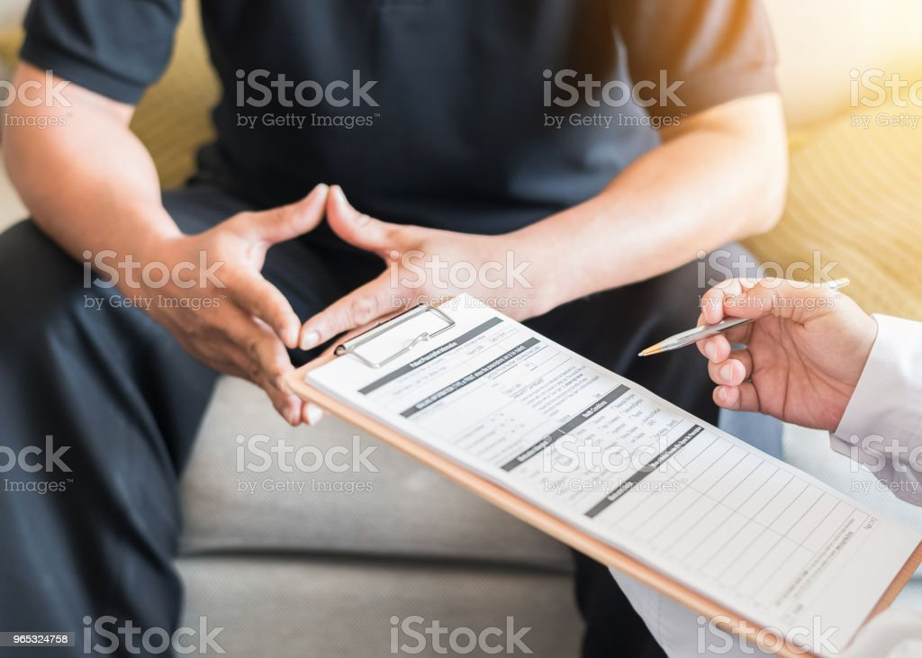 Male patient having consultation with doctor or psychiatrist who working on diagnostic examination on men's health disease or mental illness in medical clinic or hospital mental health service center royalty-free stock photo