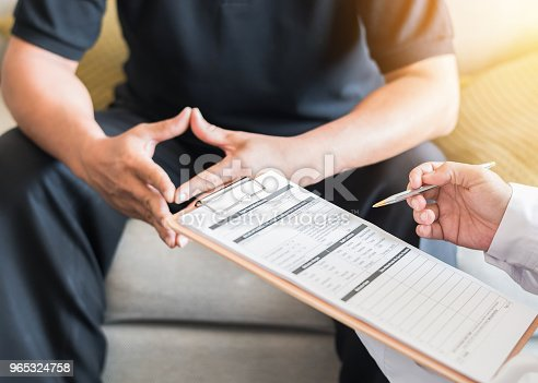 965324772 istock photo Male patient having consultation with doctor or psychiatrist who working on diagnostic examination on men's health disease or mental illness in medical clinic or hospital mental health service center 965324758