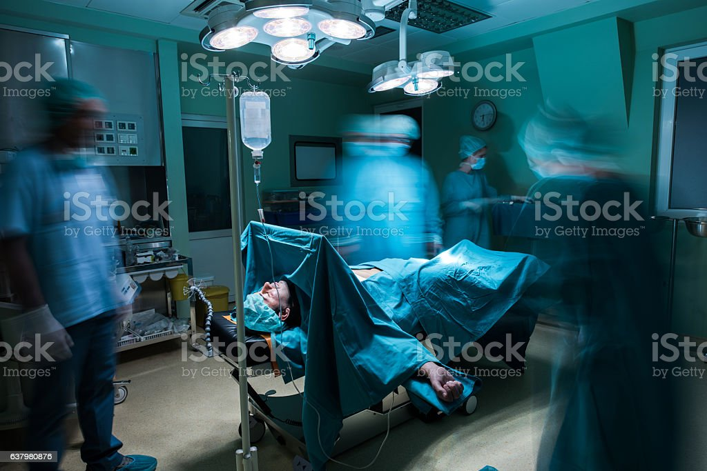 Male patient on operating table among blurred surgeons. stock photo