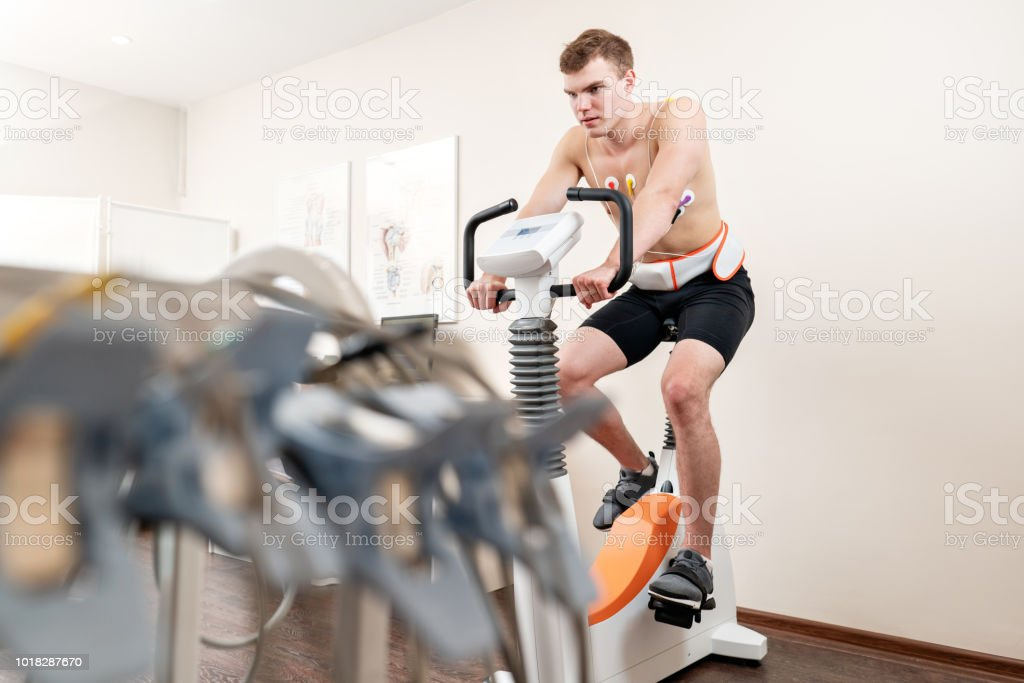 A male patient, pedaling on a bicycle ergometer stress test system for the function of his heart checked. Athlete does a cardiac stress test in a medical study, monitored by the doctor. A male patient, pedaling on a bicycle ergometer stress test system for the function of his heart checked. Athlete does a cardiac stress test in a medical study, monitored by the doctor. Athlete Performing ECG and VO2 test Adult Stock Photo