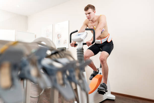 A male patient, pedaling on a bicycle ergometer stress test system for the function of his heart checked. Athlete does a cardiac stress test in a medical study, monitored by the doctor. stock photo