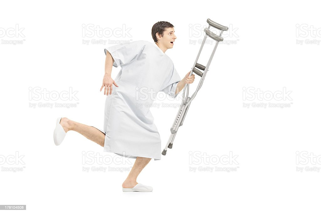 Male patient running and holding a crutch stock photo