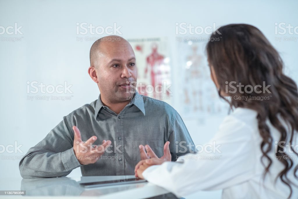 A balding male patient seeks advice from his female doctor while in...