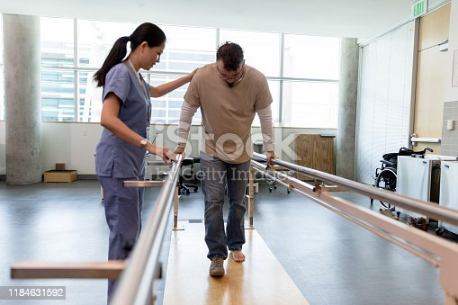 The mid adult male patient takes his first steps after foot surgery using the orthopedic parallel bars under the guidance of the female physical therapist.