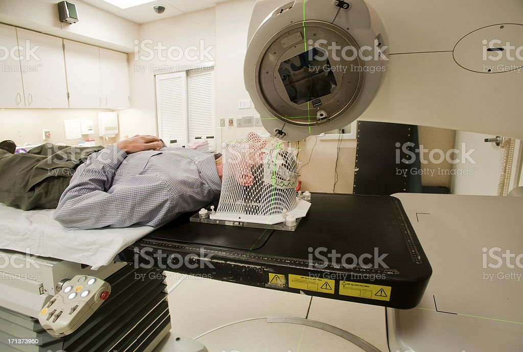 Male patient wearing a facial mask undergoing radiation stock photo