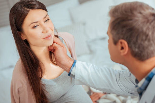 Male pediatrician checking lymph nodes of expectant mother Healthy and happy. Selective focus on a charming pregnant woman smiling while visiting her doctor and listening to him. endocrine system stock pictures, royalty-free photos & images