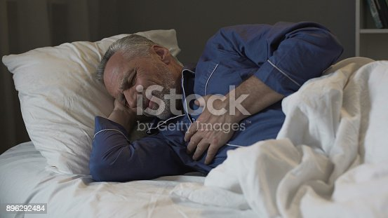 istock Male pensioner having heart attack, suffering sharp chest pain while sleeping 896292484