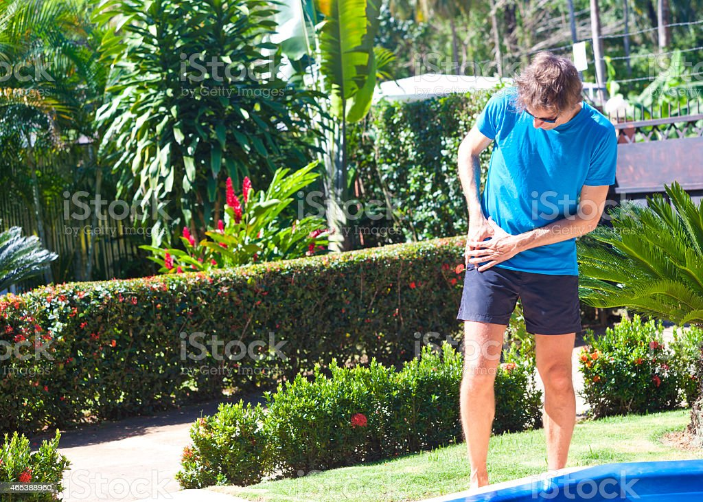 Male person with sudden hip pain in tropical surrounding stock photo