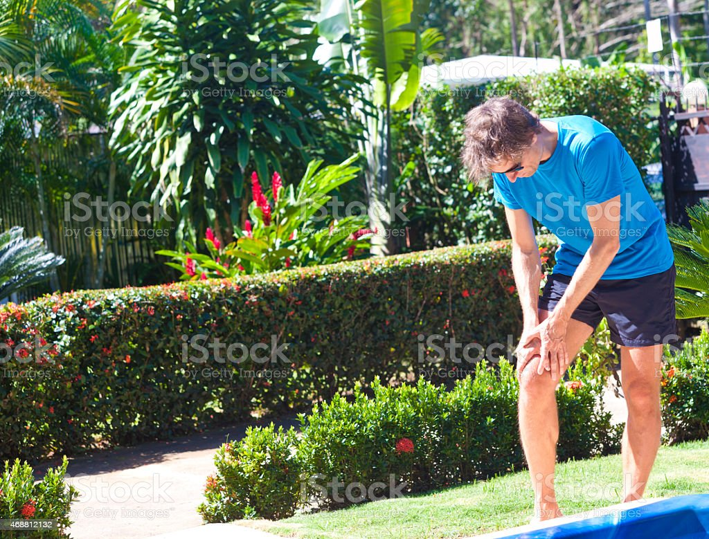 Male person with sudden knee pain in tropical surrounding stock photo