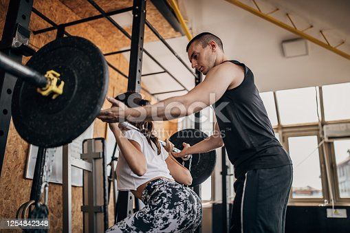 Two people, man and woman, male personal trainer assisting a woman in weight training in gym.