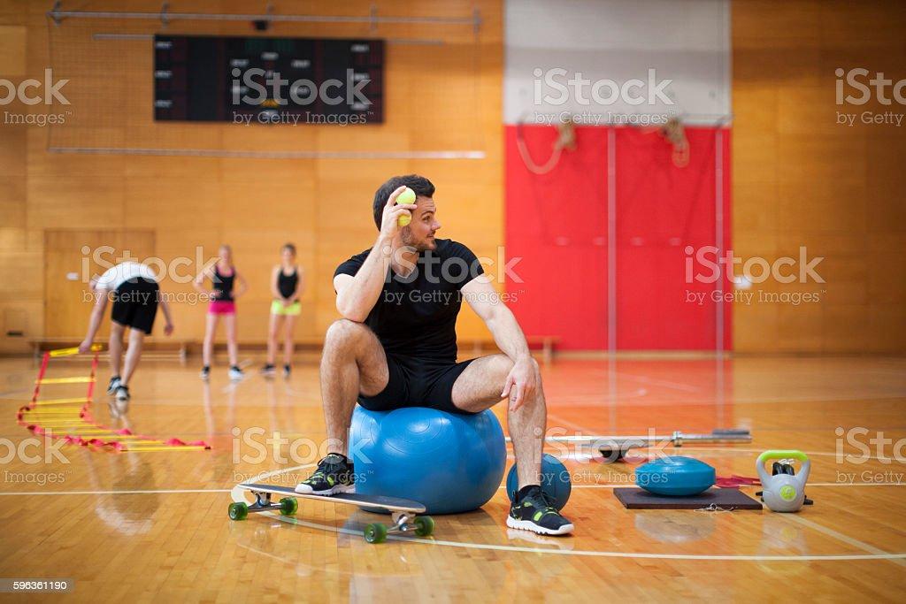 Male Personal Trainer with other Young Athletes in a Gym royalty-free stock photo