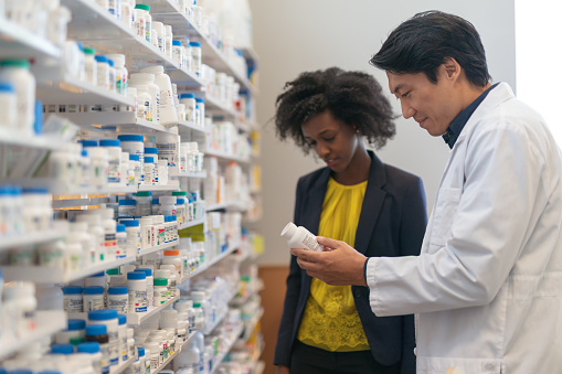 istock Male pharmacist assists woman in pharmacy 1171010137