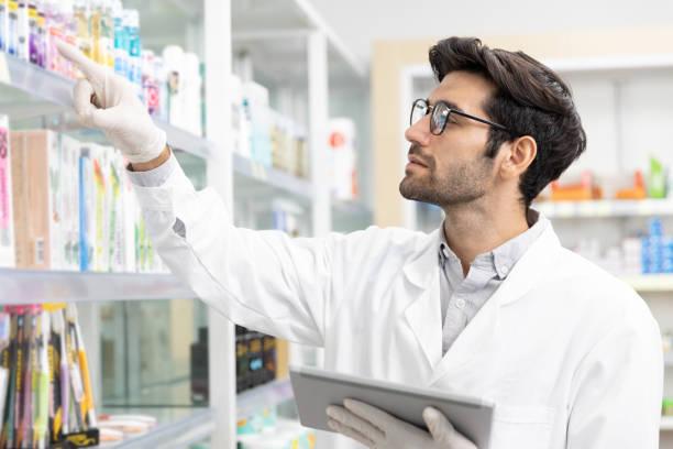 Male pharmacist checking stock drugstore using digital tablet technology in modern pharmacy. stock photo