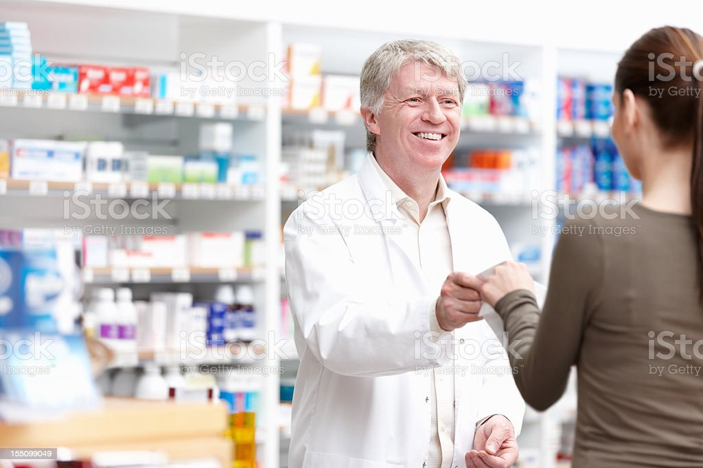 Male pharmacist giving package to customer royalty-free stock photo