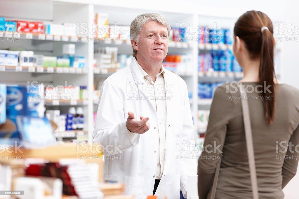 Male pharmacist speaking to customer royalty-free stock photo