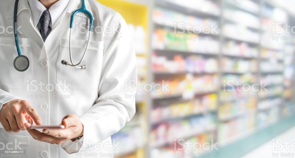 Male pharmacist using mobile phone at pharmacy. - Royalty-free Adulto Foto de stock