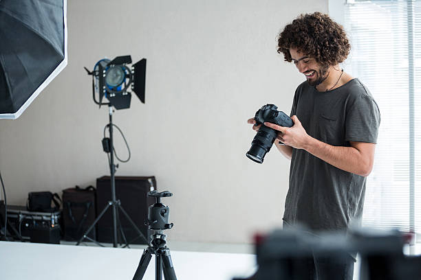 Male photographer reviewing captured photos in his digital camera stock photo