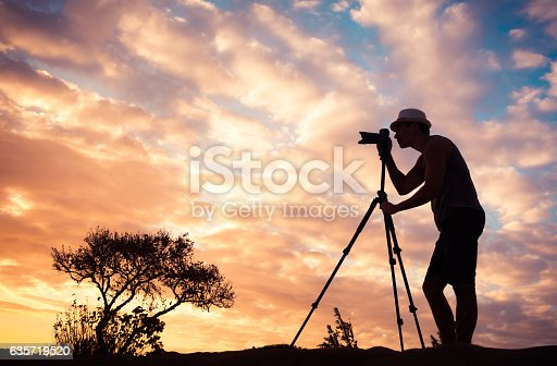 istock Male photographer taking photos in a beautiful nature setting. 635719520
