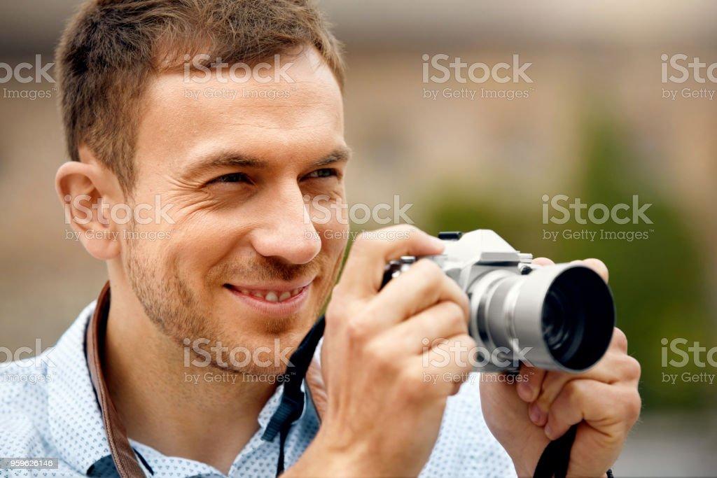Hombre fotógrafo tomando fotos en la cámara en la calle - Foto de stock de A la moda libre de derechos