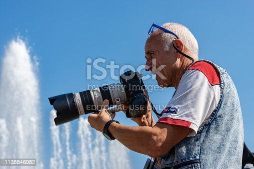 Milan, Lombardy, Italy - September 24th, 2016: Male photographer with professional equipment (Canon EOS Mark III) while he is performing a photo shoot in downtown of Milan in front of the Sforza Castle