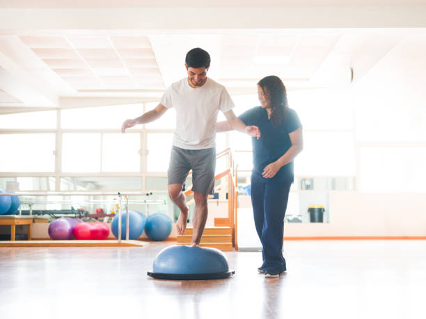 male physical rehab patient standing on bosu ball - medicina sportiva foto e immagini stock