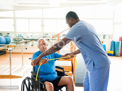istock Male physical therapist in session with elderly man on wheelchair 1132546492