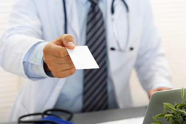 Médico masculino mão segurando e dando branco em branco cartão de chamadas - foto de acervo