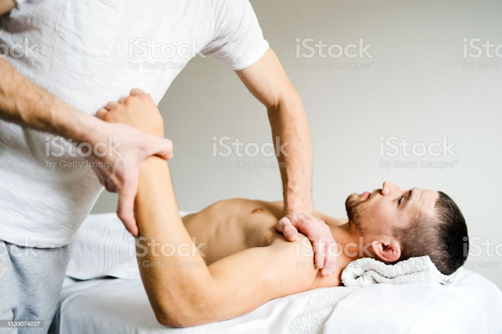 Male physio therapist giving sport massage to the young Man at the...