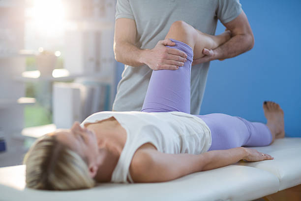 male physiotherapist giving knee massage to female patient - sports medicine stock photos and pictures