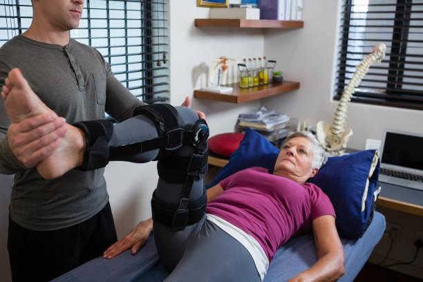 perna dando fisioterapeuta masculino massagem ao paciente - ortopedia - fotografias e filmes do acervo