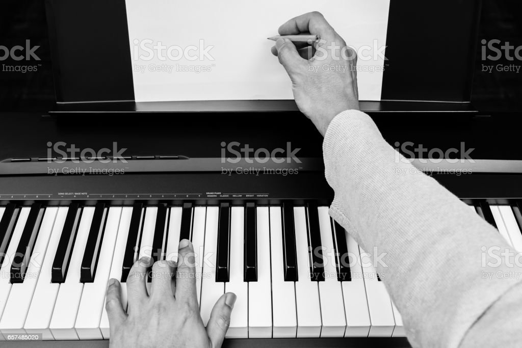 male pianist, composer, songwriter hands writing music & songs on white music sheet stock photo