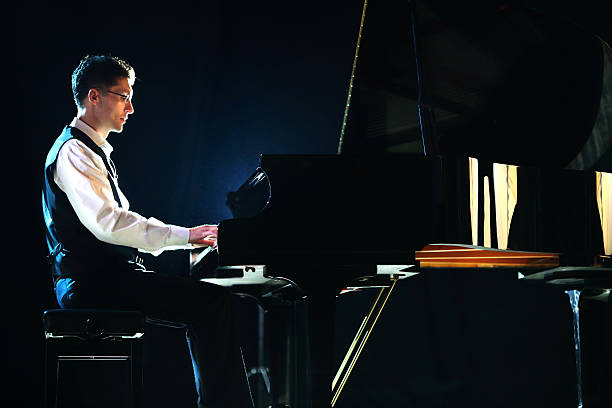 Male pianist in a concert. Side view of mid 30's male pianist playing piano in a concert. He's performing and grand concert piano at theater stage. The man is wearing black pants, white shirt and black vest. Backlit, some fill light from the side. pianist stock pictures, royalty-free photos & images