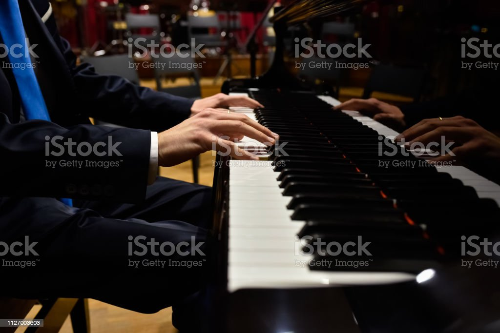 Male Pianist Playing Classical Music On A Grand Piano Stock