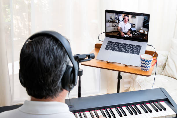 Male piano teacher giving piano lessons online at home using a laptop. stock photo