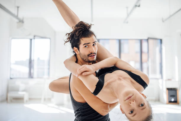 Male picking up female while dancing at studio stock photo