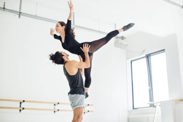 Male picking up female while practicing ballet stock photo