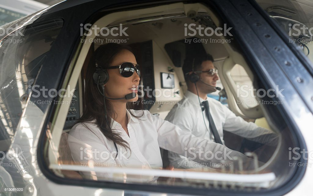 Male pilot and woman copilot traveling by helicopter stock photo