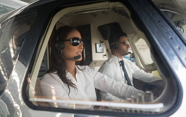 male pilot and woman copilot traveling by helicopter - flugzeug steuern stock-fotos und bilder