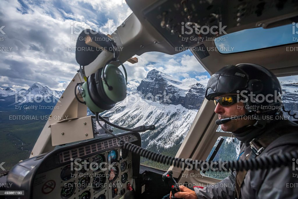 Male Pilot Flying Helicopter at Assiniboine Provincial Park, Canada stock photo