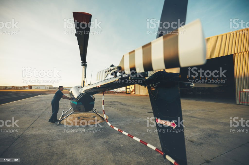 Male pilot inspecting helicopter stock photo