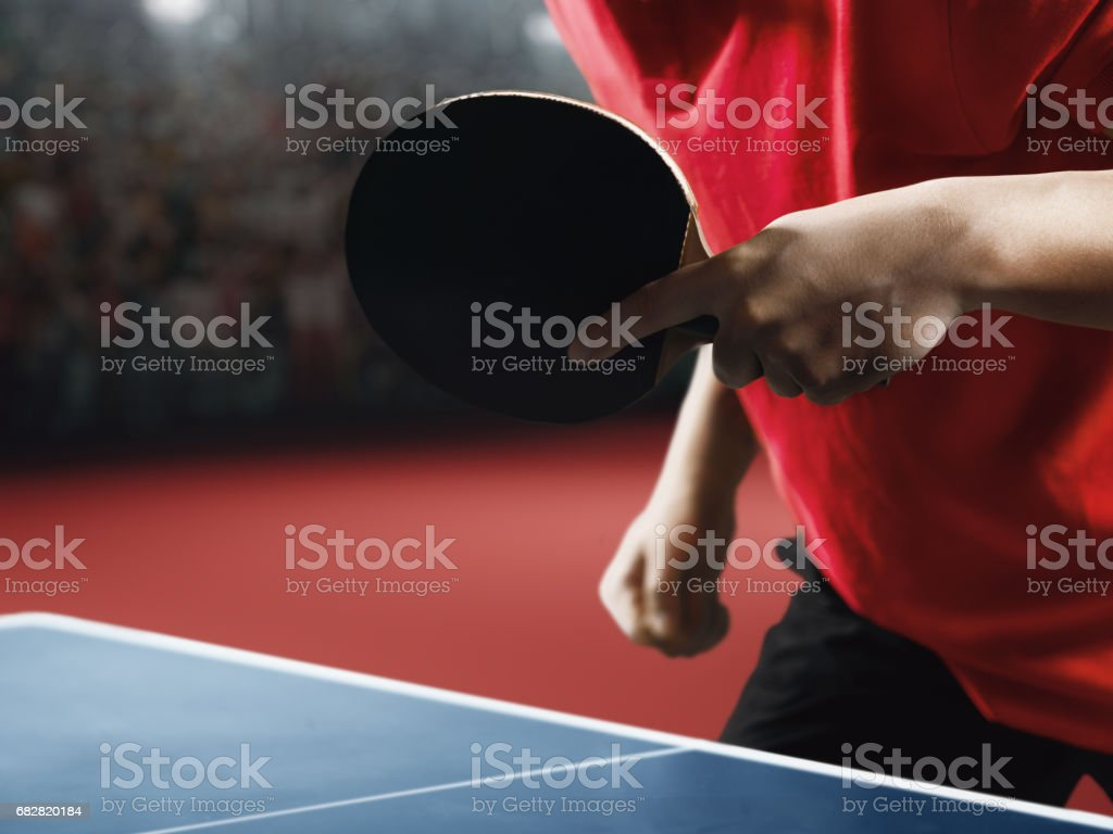 Male ping pong player holds a table tennis racket and ball stock photo