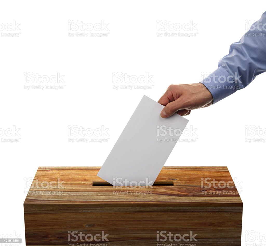 Male placing his voting envelope into a wooden ballot box stock photo