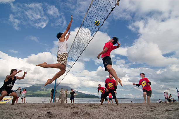 male  player jumps to spike at  a beach volleyball competition - 殺球 個照片及圖片檔