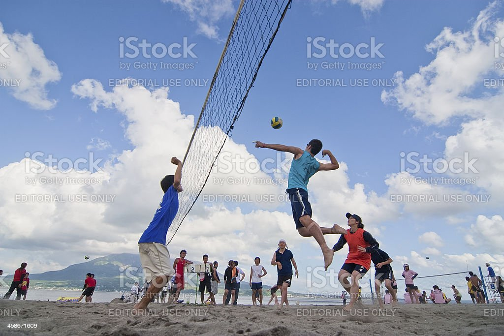 Male  player jumps to spike at  a beach volleyball competition stock photo