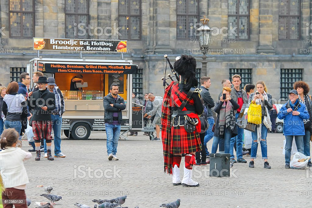 Male playing Scottish traditional pipes in historic centre of Amsterdam stock photo