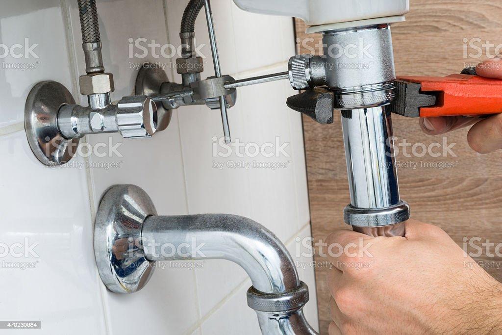 Male Plumber Fixing Sink In Bathroom stock photo