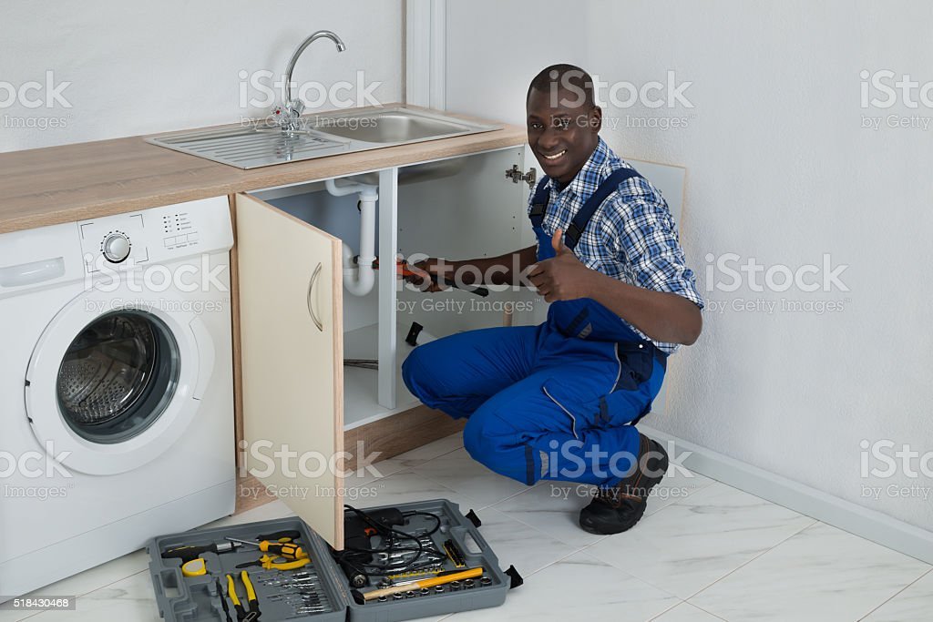 Male Plumber Fixing Sink In Kitchen stock photo