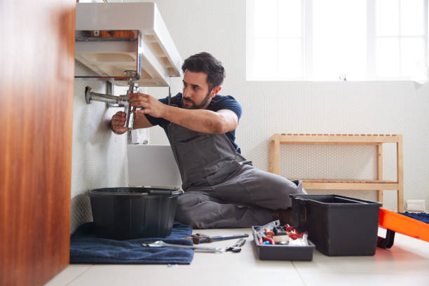 Male Plumber Working To Fix Leaking Sink In Home Bathroom stock photo