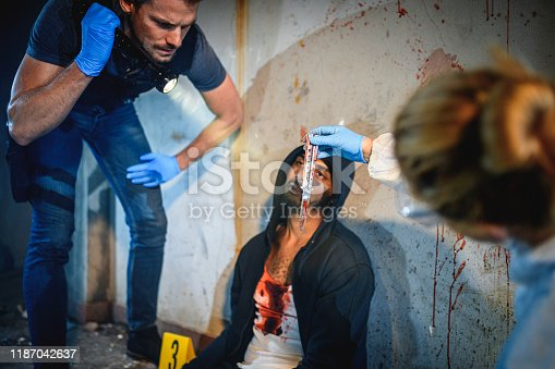 Low angle view of Caucasian male police officer standing next to African murder victim and shining flashlight on bloody knife held by forensic scientist.