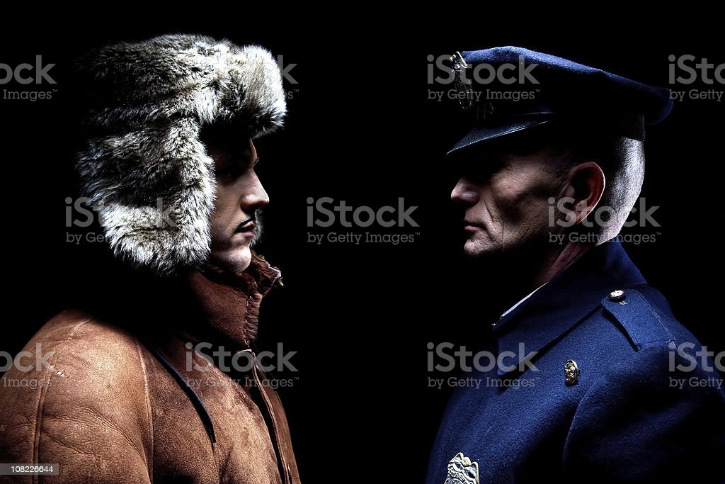 Male Police Officer Standing in Front of Young Man stock photo